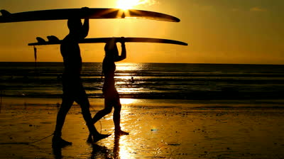 stock-footage-surfer-couple-in-silhouette-walking-with-long-surf-boards-at-sunset-on-tropical-beach